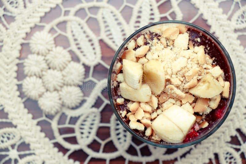 Dessert délicieux avec le pudding de banane et de chocolat de biscuits dans la tasse en verre sur la vue supérieure de table photos stock