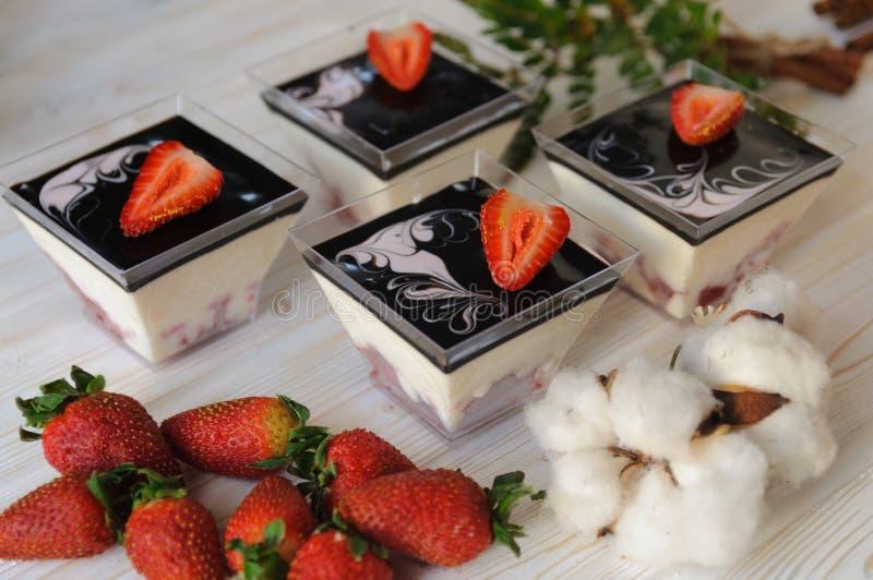 Dessert de crème anglaise dans un verre avec les fraises fraîches sur le fond blanc image libre de droits