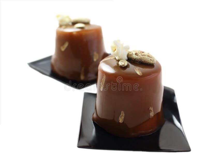 Dessert del caffè e del cioccolato con la glassa dello specchio, i punti di cacao ed il popcorn sui sottobicchieri neri fotografie stock libere da diritti