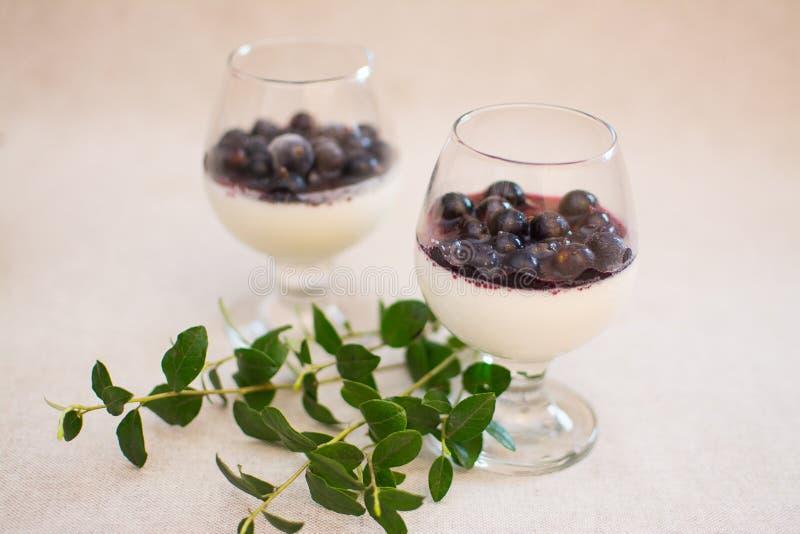 Dessert del latte con l'inceppamento del mirtillo e le bacche fresche immagini stock libere da diritti