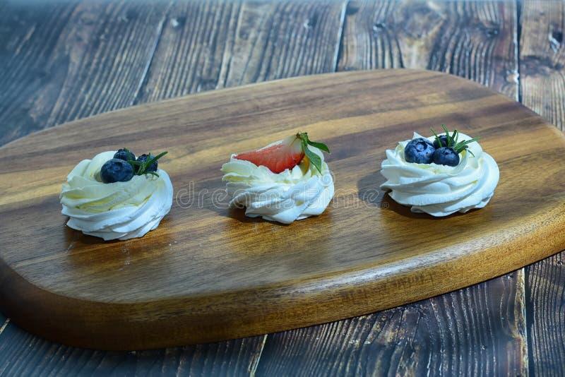 Dessert del merengue di Pavlova sulla tavola di legno ciò è dessert fatto di merengue e delle bacche rotondi casalingo, delizioso immagine stock