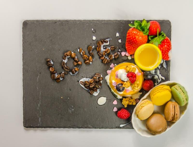 Dessert delizioso su un piatto di pietra nero con budino e il macaro immagine stock