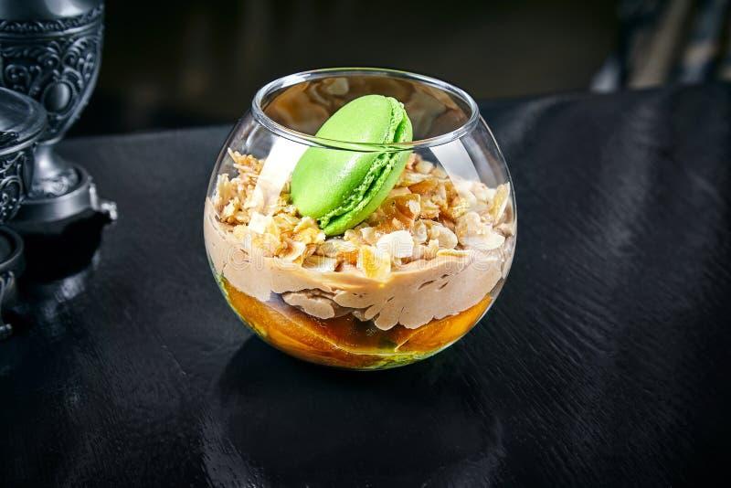 Dessert dell'albicocca con il maccherone in un barattolo budino con l'albicocca e la mandorla Fine sul fondo dolce dell'alimento  fotografie stock libere da diritti