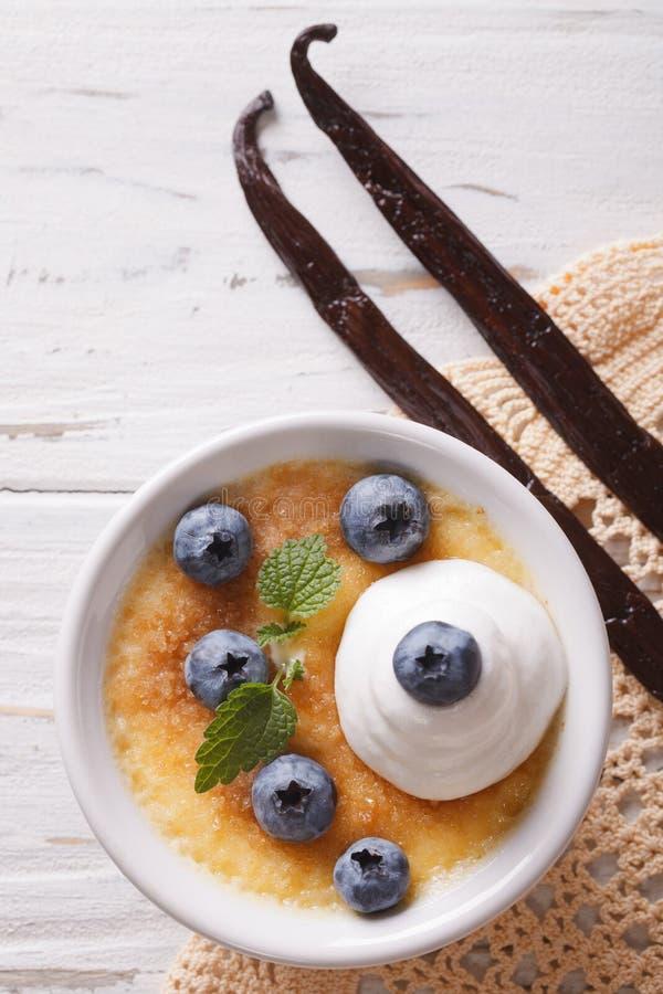 Dessert della crème-brulée con il primo piano dei mirtilli Vista superiore verticale fotografia stock libera da diritti