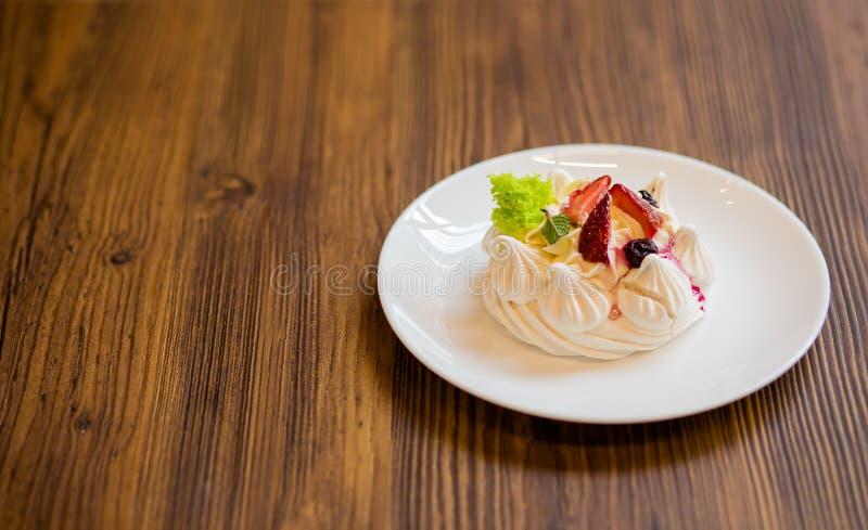 Dessert della meringa di Pavlova sulla tavola di legno scura Dessert bianco aerato fatto di merengue e della fragola rotondi sull fotografia stock libera da diritti