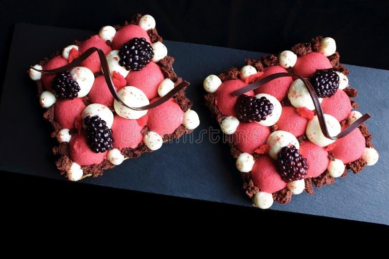 Dessert della pasta sfoglia della mousse e della mora del ribes con le decorazioni a spirale montate del cioccolato e del ganache immagini stock