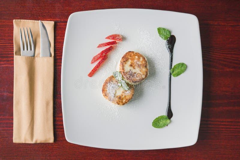 Dessert della prima colazione - torta con la ricotta, sous dolce verde e fragola e coltelleria immagini stock libere da diritti