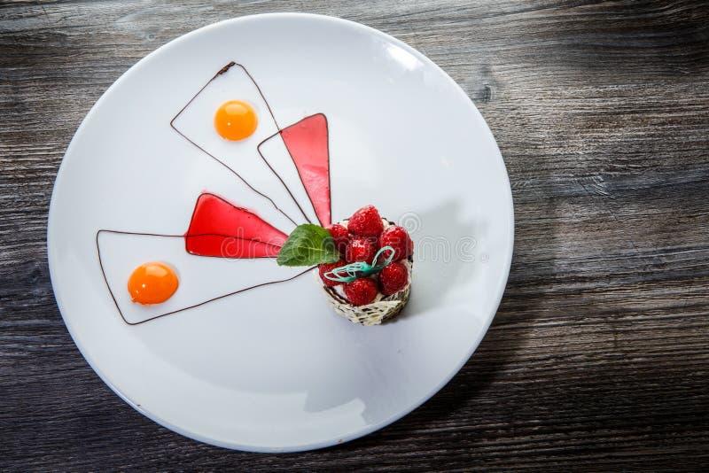 Dessert di materiale da otturazione originalmente decorato della crema del lampone del cioccolato immagine stock libera da diritti