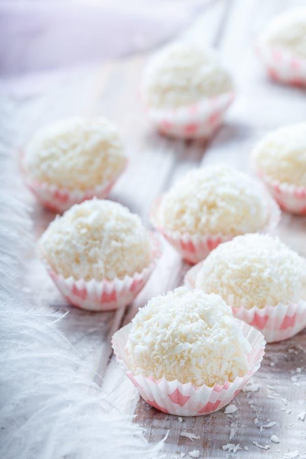 Dessert fait maison de sucrerie de truffes blanches arrosé dans des puces de noix de coco sur la fin en bois de fond  Praline dél photographie stock libre de droits