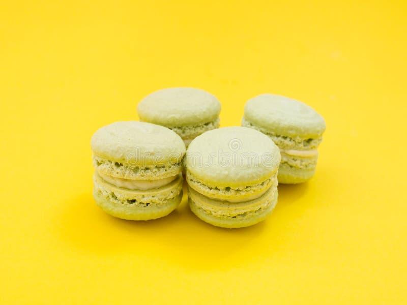 Dessert français délicieux de macaronis verts sur le fond jaune Saveur de pistache photos stock
