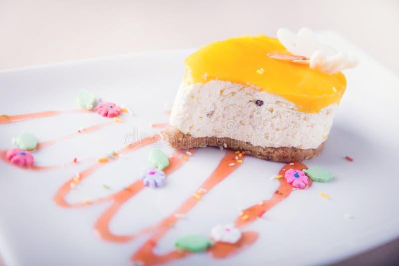 Dessert - gâteau au fromage orange avec la décoration mignonne sur Backgr blanc photographie stock libre de droits