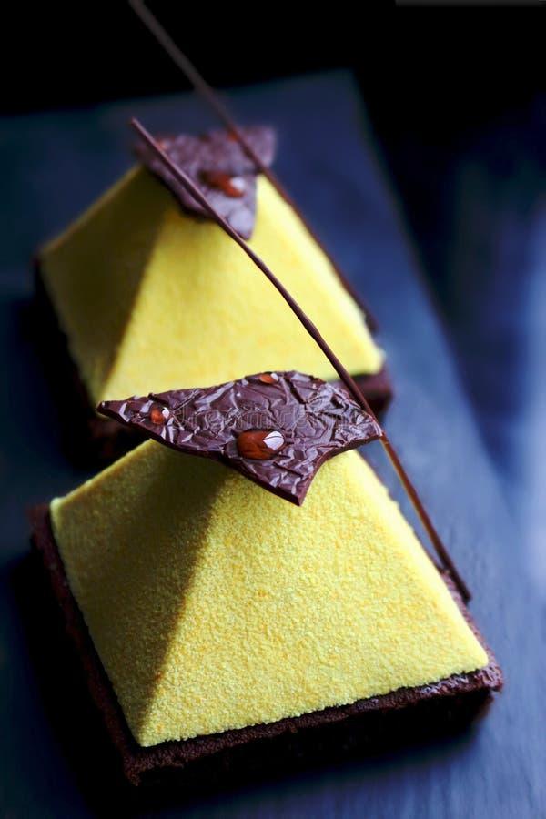Dessert giallo della piramide sul fondo scuro del brownie fotografia stock