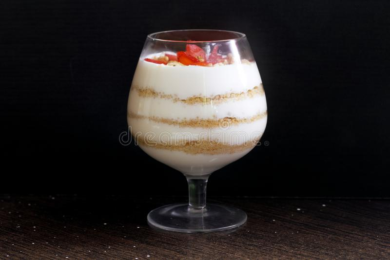 Dessert in a glass goblet. Layers laid biscuit crumbs and cream. Decorated with strawberry slices. With the addition of walnut. On. A dark background royalty free stock images