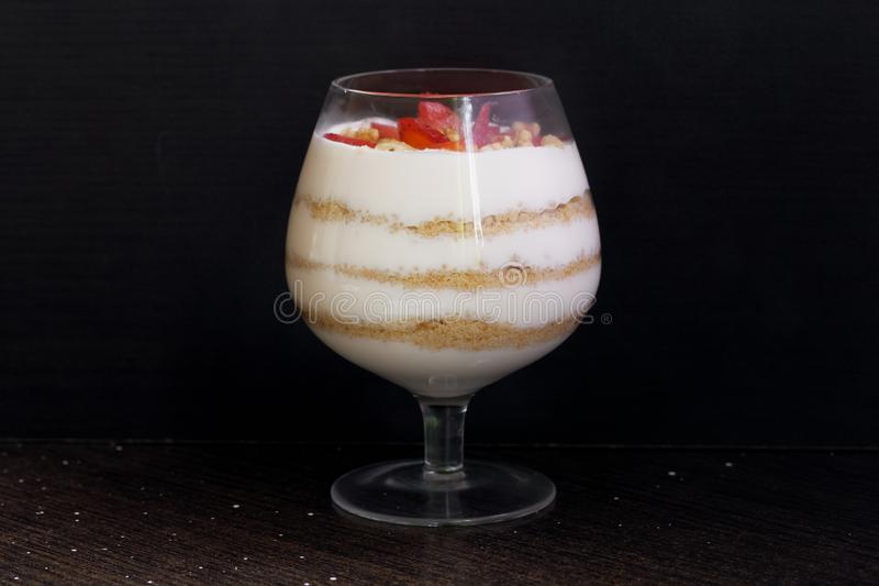 Dessert in a glass goblet. Layers laid biscuit crumbs and cream. Decorated with strawberry slices. With the addition of walnut. On. A dark background stock image