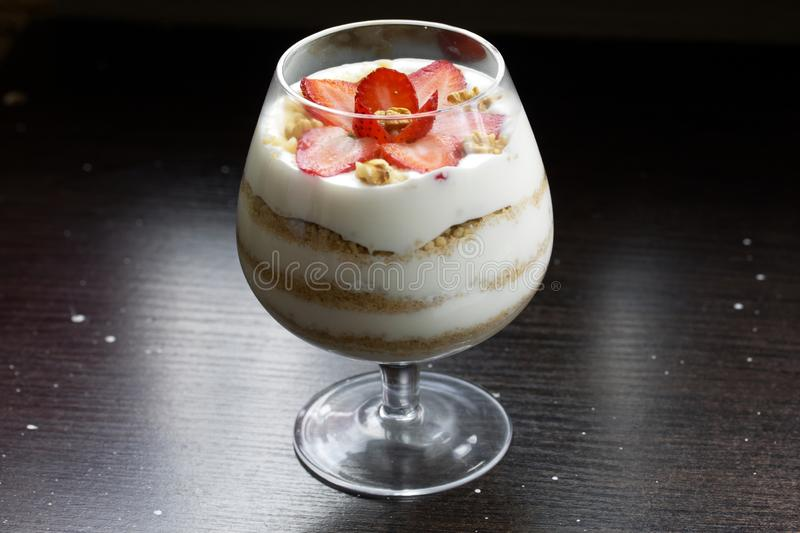 Dessert in a glass goblet. Layers laid biscuit crumbs and cream. Decorated with strawberry slices. With the addition of walnut. On. A dark background stock photo