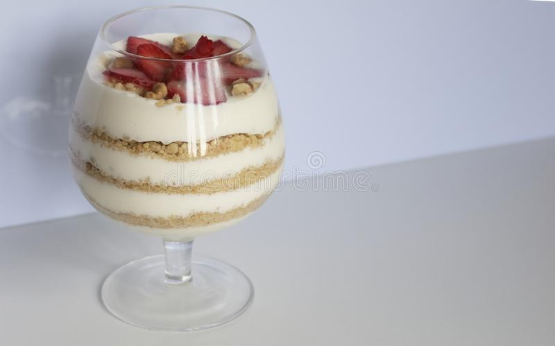 Dessert in a glass goblet. Layers laid biscuit crumbs and cream. Decorated with strawberry slices. With the addition of walnut. On. A white background royalty free stock image