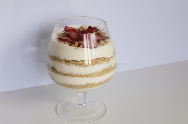 Dessert in a glass goblet. Layers laid biscuit crumbs and cream. Decorated with strawberry slices. With the addition of walnut. On. A white background royalty free stock photos