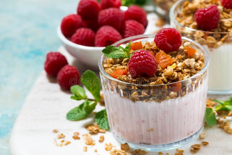 Dessert with homemade granola, fresh raspberries, fruit. And natural yoghurt, closeup horizontal royalty free stock photo