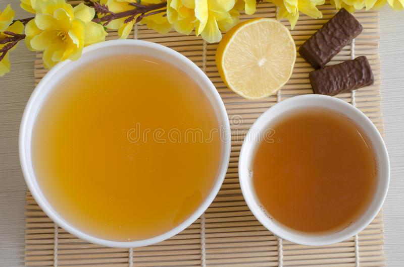 Dessert - honey and green tea. Artificial yellow flowers stock images