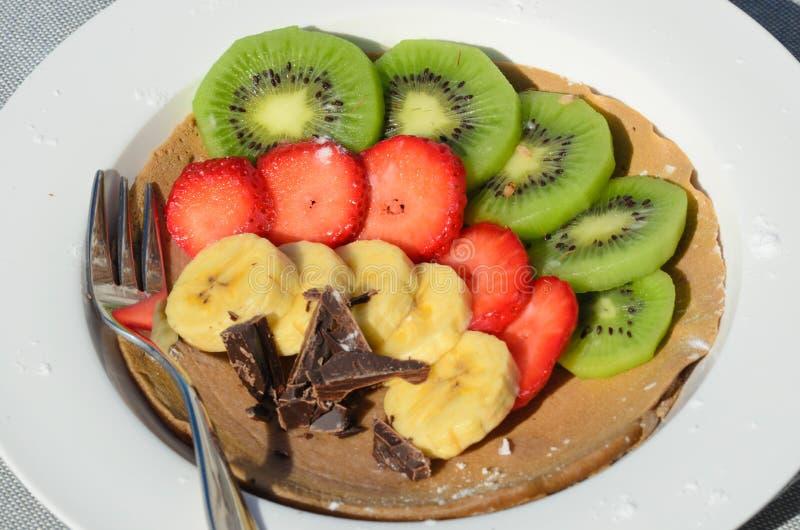 Dessert of kiwi, strawberry, banana and chocolate with fork stock image