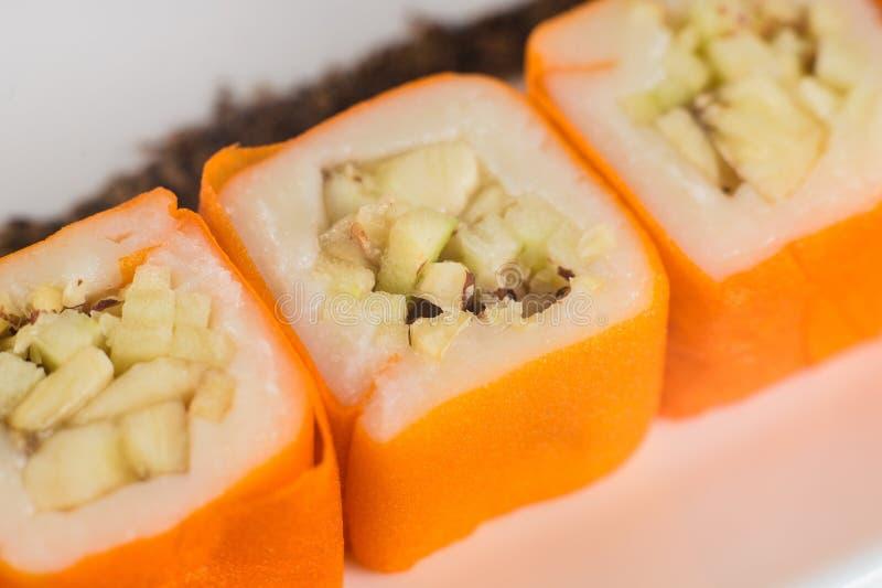 Dessert Maki Sushi - rotoli con varia frutta in budino di riso e la noce di cocco si sfalda fotografia stock libera da diritti