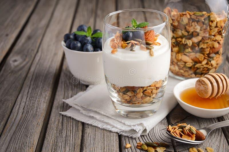 Dessert met eigengemaakte granola, yoghurt en bosbessen op rustieke achtergrond stock afbeelding