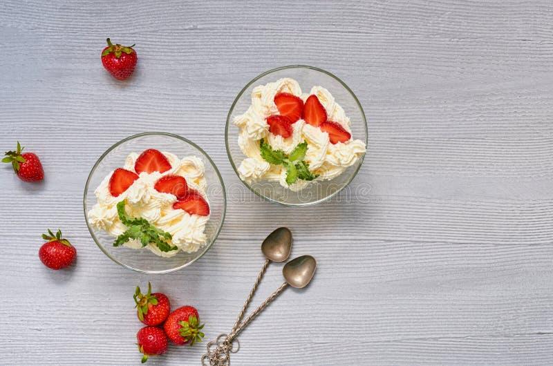 Dessert met gesneden aardbeien en roomkaas in de glaskommen op een grijze achtergrond met exemplaarruimte royalty-vrije stock foto's