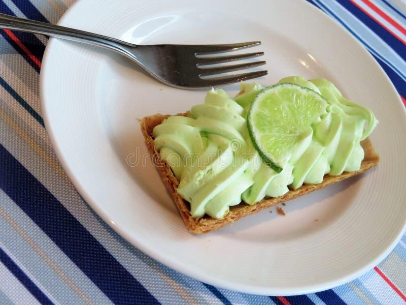 Dessert operato della torta della calce chiave con una fetta di calce fotografia stock
