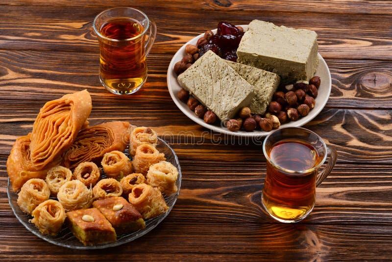 Dessert orientali tradizionali assortiti con tè su fondo di legno immagine stock
