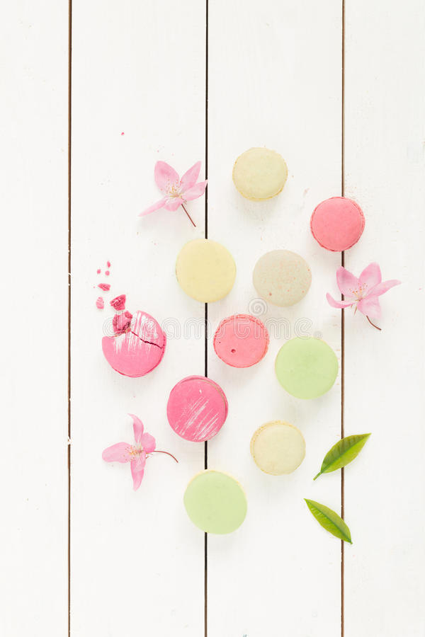 Dessert - pastel french macarons cakes on rustic white. Dessert - pastel french macarons (meringue cakes) on rustic white wooden background. Flat lay composition royalty free stock image