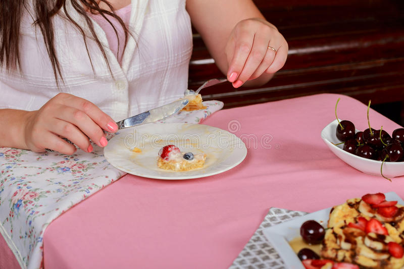 dessert and people concept - close up of woman eating waffle with strawberry stock image