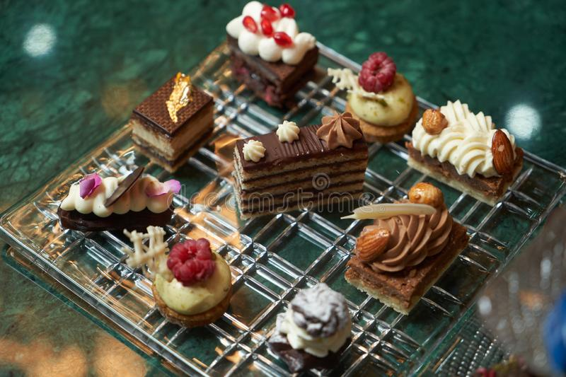 Dessert plate with assortment of sweets, piece of cake, cookies, biscuits royalty free stock images