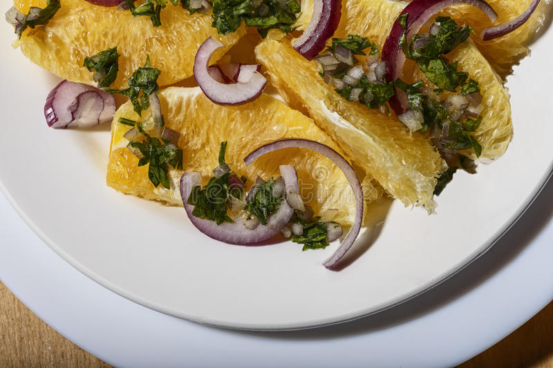 For dessert, the salad of oranges with red onions, parsley and olive sauce. Oranges are widely used in vitamin salads in cooking different peoples stock photos