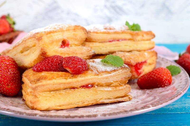 Dessert saporito dolce della pasta sfoglia sul piatto su fondo di legno Biscotti casalinghi deliziosi fotografia stock libera da diritti