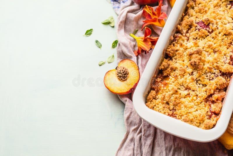 Dessert squisito della briciola della pesca in teglia da forno su fondo leggero, vista superiore Spazio della copia per la vostra fotografia stock libera da diritti