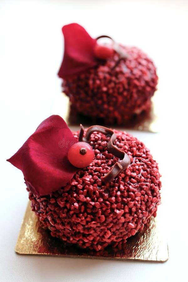 Dessert strutturati rossi con le bacche del ribes ed il petalo di rosa rossa commestibile fotografie stock
