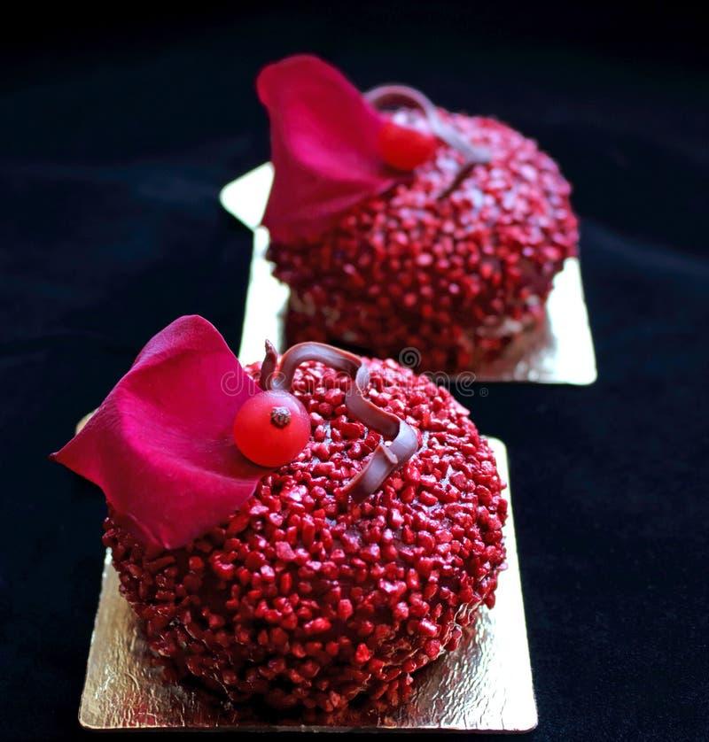 Dessert strutturati rossi con le bacche del ribes ed il petalo di rosa rossa commestibile fotografia stock