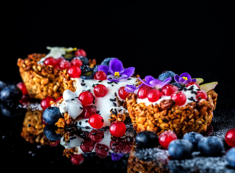 Dessert with sunflower seeds, yogurt and fresh berries. On black royalty free stock images