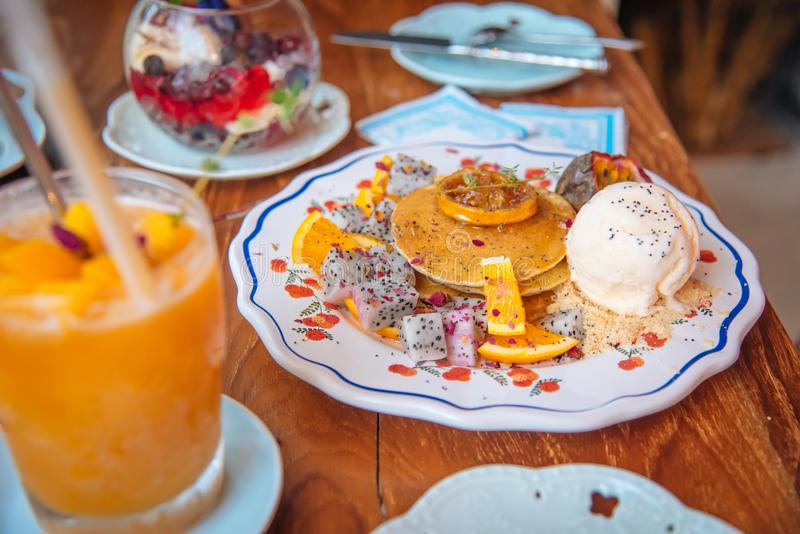 Sweet Pancakes with honey and vanilla ice cream Fruit with Orange focus on pancake royalty free stock photography