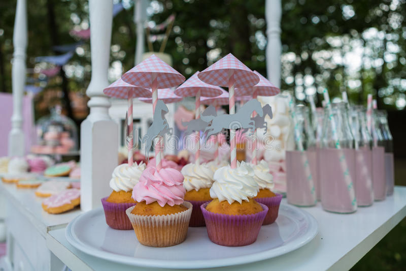 Dessert table for a party. Cake, cupcakes, sweetness and flowers. Shallow dof stock photography