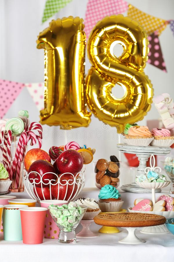 Dessert table in room with golden balloons for 18 year birthday party. Dessert table in room decorated with golden balloons for 18 year birthday party royalty free stock photography