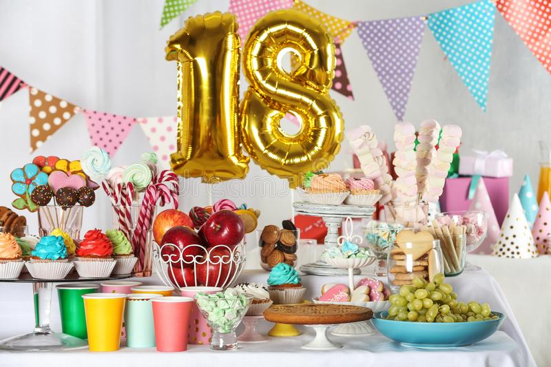 Dessert table in room decorated with balloons for 18 year birthday party. Dessert table in room decorated with golden balloons for 18 year birthday party royalty free stock photos