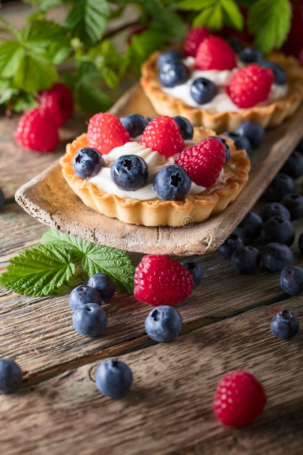Dessert tarts with raspberries and blueberries on a wooden tabl royalty free stock photo