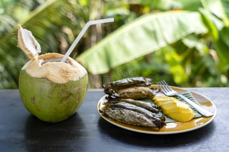 Dessert thaïlandais de style, mangue jaune avec du riz collant de banane dans les palmettes et noix de coco verte La mangue jaune images stock