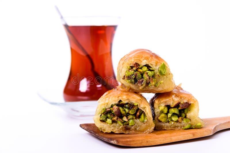 Dessert turc traditionnel, baklava du plat en bois avec des pistaches et thé turc avec la cuillère sur le blanc photo stock