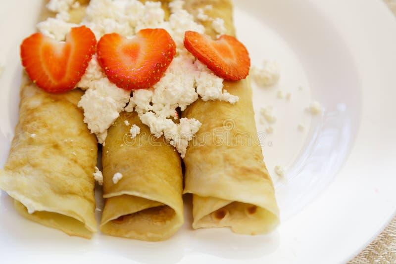 Dessert van pannekoeken wordt met kwark en aardbeien worden gevuld gemaakt die Is op een lijst in een witte plaat Sluit omhoog royalty-vrije stock afbeeldingen