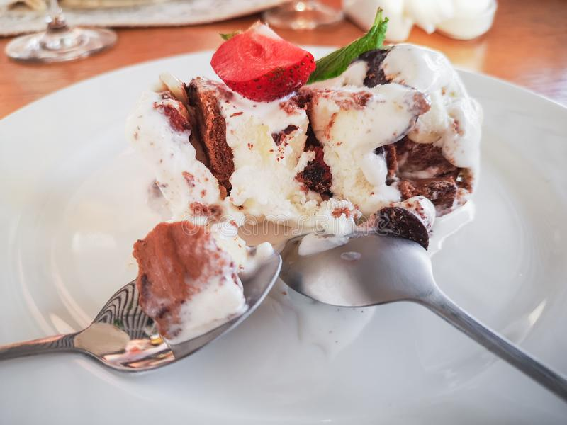 Dessert from vanilla ice cream, doused with chicolade with strawberries and mint leaves on a white plate. Steel appliances on a stock photos