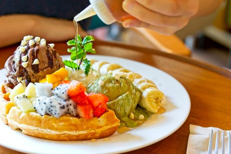 Dessert, waffles served with mixed fruits, sliced banana, chocolate ice-cream and green tea ice-cream royalty free stock photography