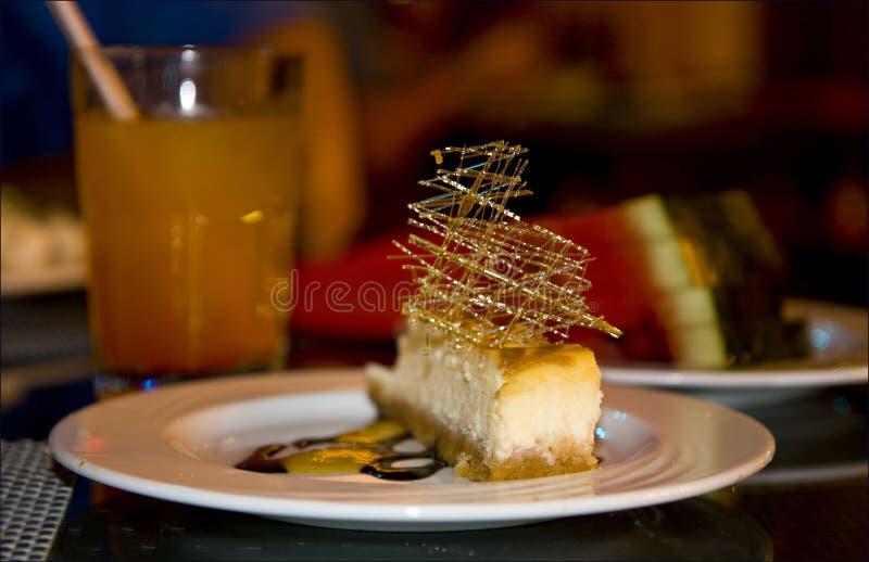 Dessertcake met karamel en room op de plaat en het jus d'orange, voedselfotografie stock foto