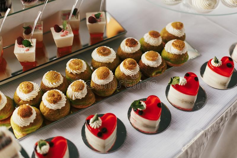 Desserts blancs et de chocolat avec les fruits et le crem, petits gâteaux sur le support, table douce moderne au mariage ou fête  photographie stock libre de droits
